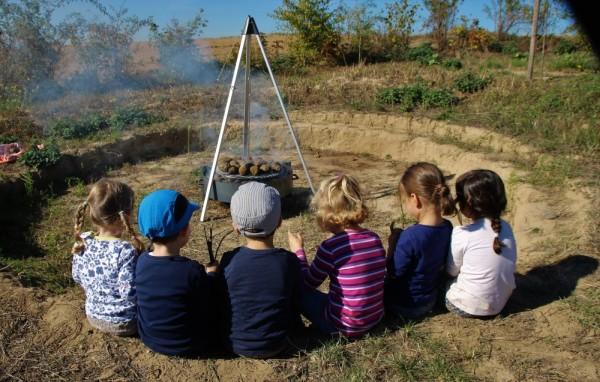 Kinder am Dreibein am offenen Feuer